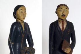 Beschilderd Indisch houten beelden van een Indonesische ambtenaar en Javaanse vrouw op voetstuk. De beelden zijn afkomstig van studenten van de Rijks Belasting Academie uit Indonesië. De batik op de sarong van de ambtenaar geeft aan dat hij van (lage) adel is. [Dit hebben we nog in onderzoek via Maarten Manse].